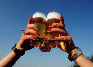 Hände halten drei Bier gegen den blauen Himmel